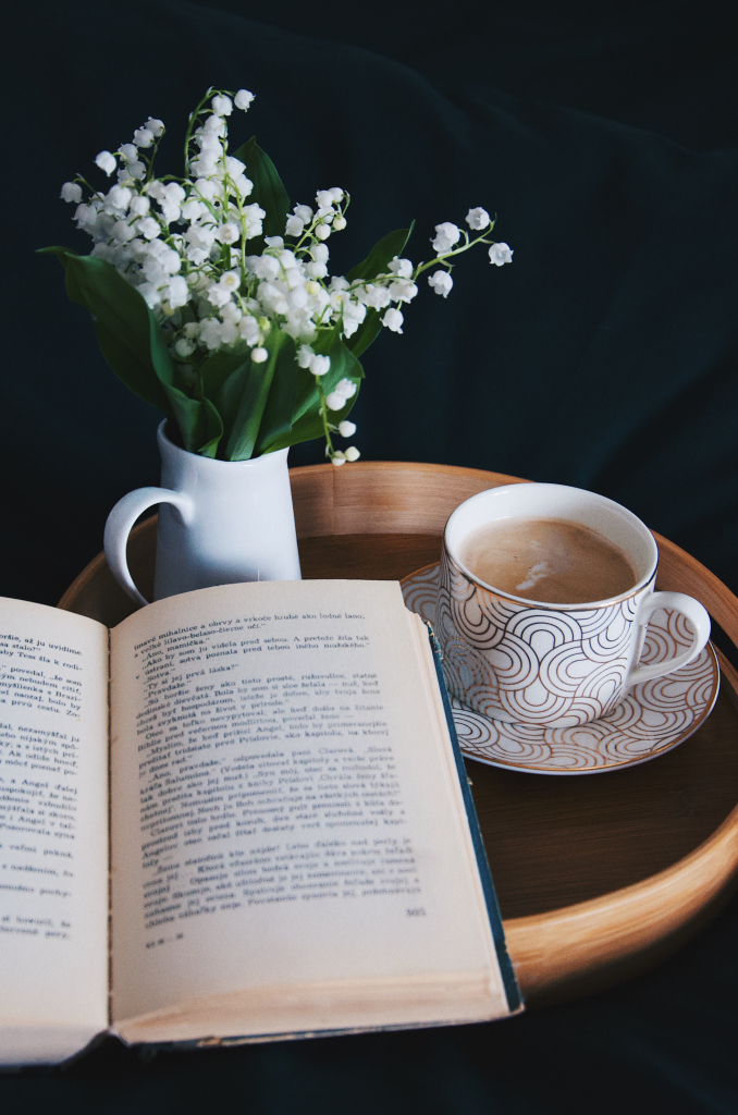 Table with book, flowers and coffee